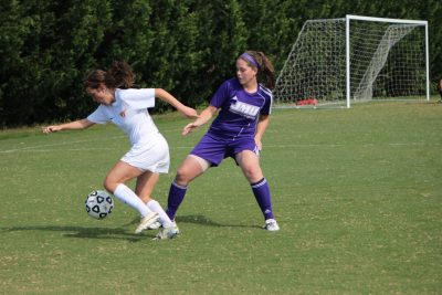 a Virginia Tech women's soccer player battles a JMU player on the upper SRA fields