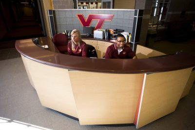 two students work the check in desk at McComas Hall