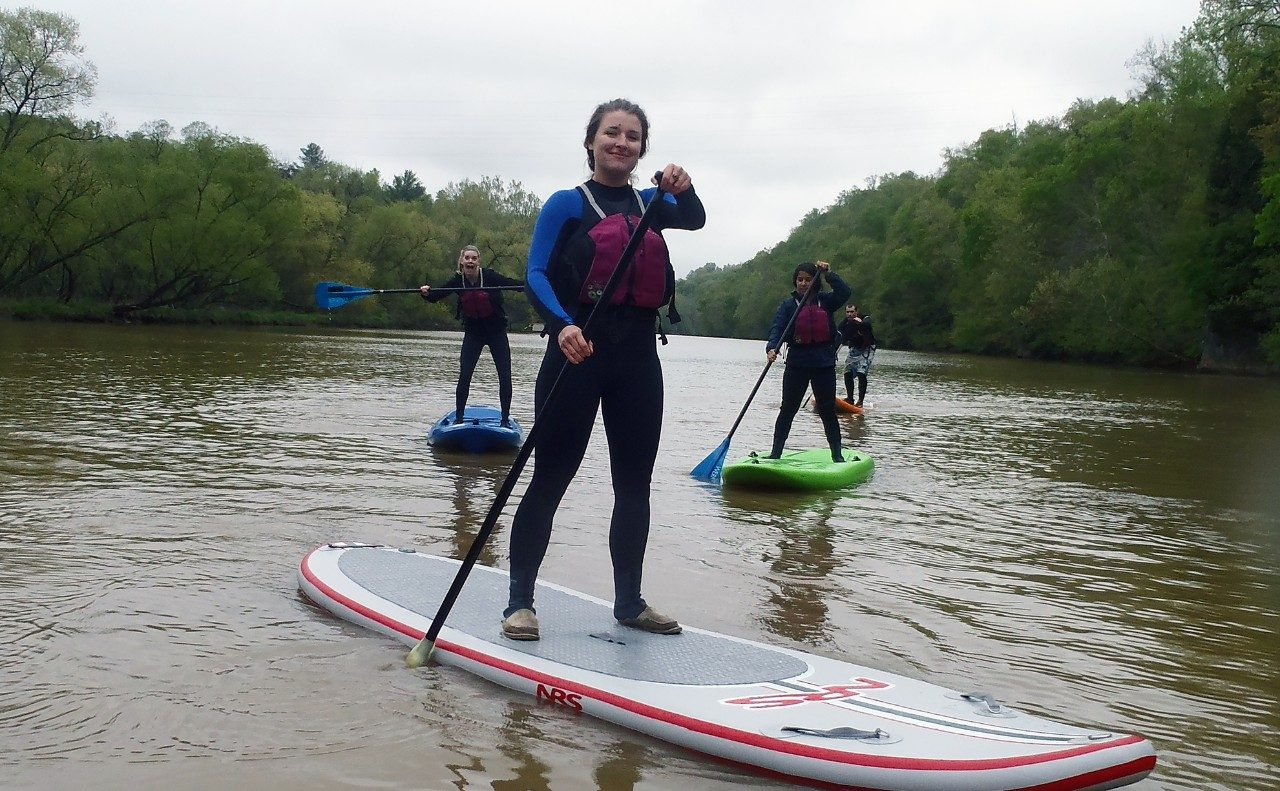 students stand up paddleboarding on a river